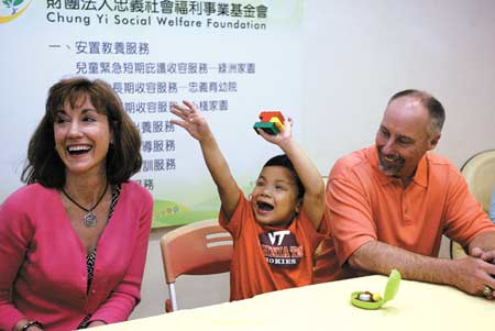 """Margaret Weddle, left, and her husband L. Garrett Weddle smile while their adopted son """"Joe"""" flings his arms in enthusiasm during a media event yesterday in Taipei City. (CNA)"""